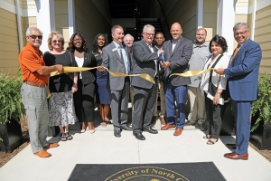 Chancellor Robin Gary Cummings (far right) joins university and town officials during a ribbon-cutting ceremony marking the expansion of University Courtyard Apartments.