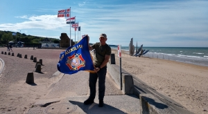 Jon Ring holds the VFW Auxiliary flag on Omaha Beach while touring Normandy for the 75th anniversary of D-Day.