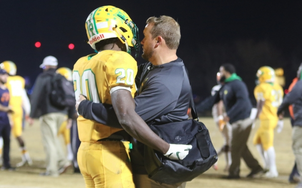 Senior Dereck Barringer (20) hugs WR coach Andy Shuler following Richmond's fourth-round playoff game.