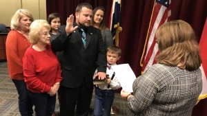 Commissioner Ben Moss takes the oath of office from Dena Cook, board clerk, while his son Sam holds the Bible and other family members stand behind in support.