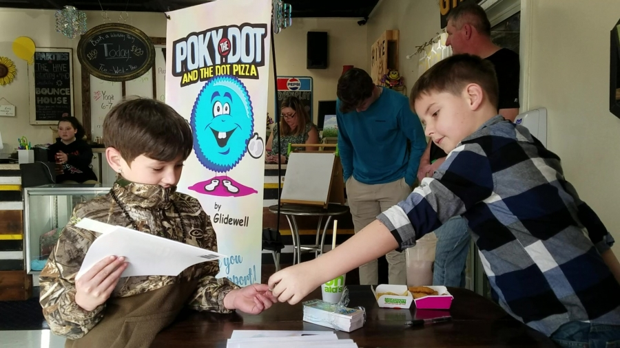 "Ethan Glidewell exchanges a copy of his book, ""Poky the Dot and the Dot Pizza,"" for $10 with classmate Aydden Covington during a book signing Tuesday afternoon at The Hive."
