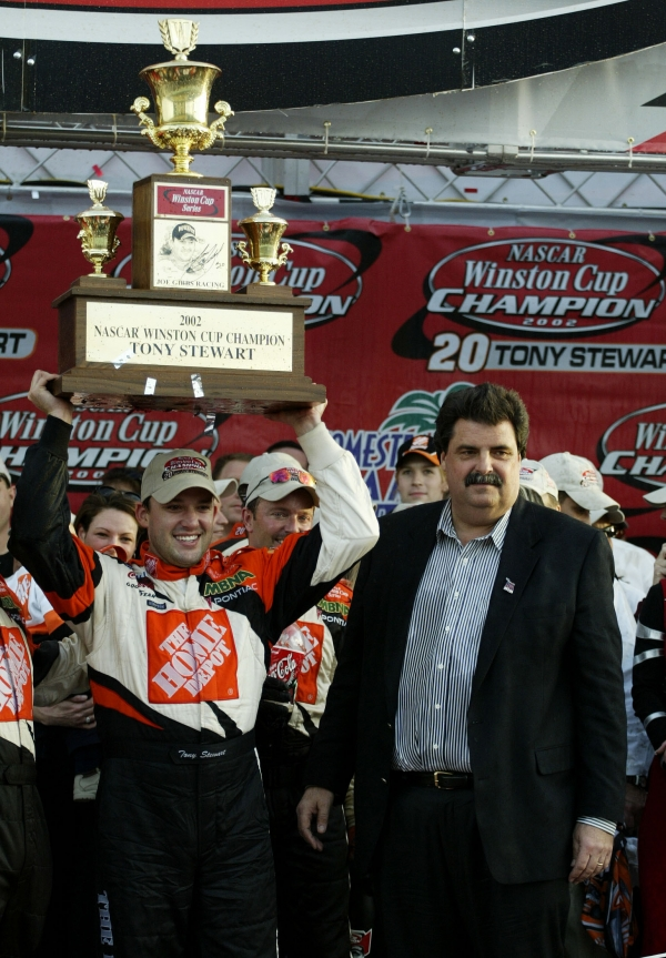 Tony Stewart, driver of the #20 Home Depot Pontiac Grand Prix lifts the NASCAR Winston Cup Championship Trophy as NASCAR President Mike Helton looks on after Stewart won the Monster Energy NASCAR Cup Series Championship at the Ford 400 at the Homestead-Miami Speedway on November 17, 2002 in Homestead, Florida.