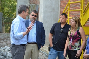 Gov. Roy Cooper speaks with County Manager Bryan Land and Chris Fowler and Christy Leviner of von Drehle after surveying a washout at the Cordova plant.