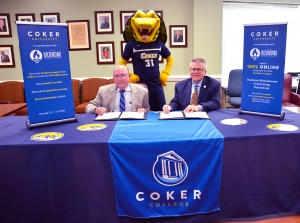 Dr. Dale McInnis, president of Richmond Community College, and Dr. Robert L. Wyatt, president of Coker College, sign the articulation agreement that creates a bridge program between the two institutions. Also attending the signing was Coker's mascot, Striker.