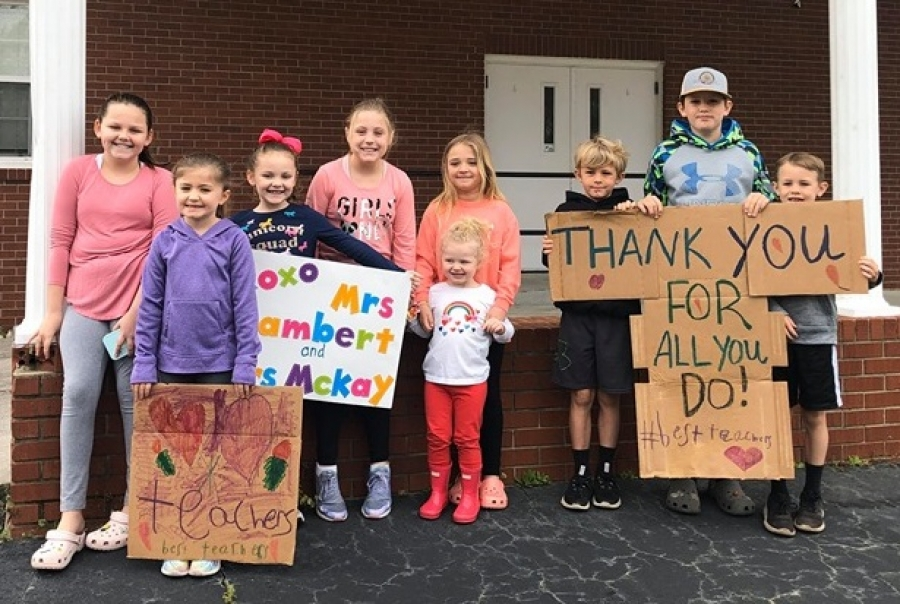 A group of students from L.J. Bell Elementary hold signs cheering on their teachers who paraded through the school's service area Tuesday.