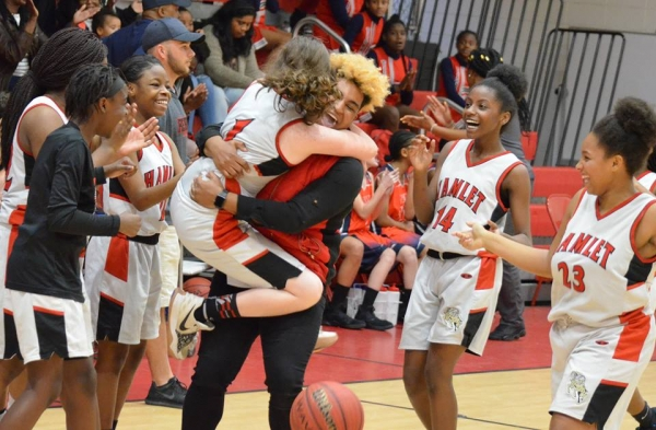 Ryelan Lyerly (1) jumps into Deondra Morrison's arms after the final buzzer sounded during Monday's win.