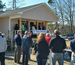 Ellis and Nikki Pittman stand on the porch of their new home Saturday during a dedication ceremony. The house was the first Women Build by Habitat for Humanity of the NC Sandhills.