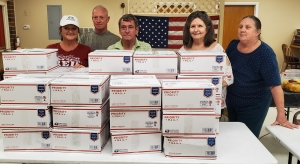 Members of VFW Post 4203 and its Auxiliary stand behind 31 care packages bound for Thule Air Base in Greenland. Pictured, from left: Auxiliary President Robin Roberts; Post Senior Vice Cmdr. Tim Grooms; Post Quartermaster Vernon Labore; Auxiliary Jr. Vice President Kay Jones; and Auxiliary Conductor Clarice Lynn.