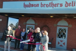 Rex Hudson cuts a red ribbon held by Rockingham Mayor Steve Morris and Richmond County Chamber of Commerce President Emily Tucker for the ceremonial reopening of Hudson Brothers Deli on Tuesday.