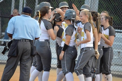 The Lady Raiders celebrate at home plate following Greyson Way's grand slam home run in Tuesday's SAC tournament opening round win over Seventy-First.