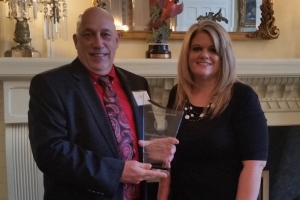 Therafirms's Ken Hartley, VP of N.C. Operations, and Leigh Ann Locklear, Sales Operations Manager, with Top Rural Exporter Award at Governor's Mansion.