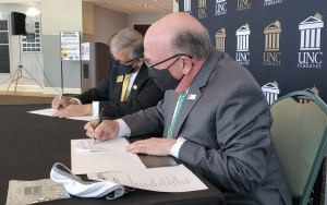 UNC Pembroke Chancellor Dr. Robin Cummings, left, and Richmond Community College President Dr. Dale McInnis sign an agreement at Cole Auditorium Thursday that will ease the transition for students who plan to become teachers.