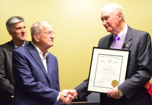 Outgoing Commissioner Thad Ussery, right, shakes hands with his friend, G.R. Kindley, after receiving the Order of the Long Leaf Pine from Gene McLaurin.