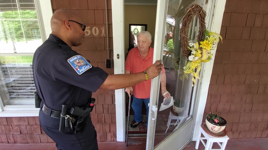 "Hamlet Police Chief Tommy McMasters stops at a home Saturday to hand out contact information and ask if there have been any issues in the area during the department's first phase of ""Neighborhood Sweep."" See video of the effort on the RO's Facebook page."
