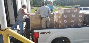 Therafirm employee Mark James helps Richmond County Schools employees load boxes of masks for students and staff.