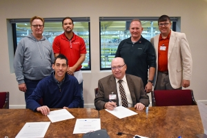 Rob Schmalbach, vice president of Field Production for VBC Manufacturing, and Dr. Dale McInnis, president of Richmond Community College, sign a partnership for customized training. Pictured in back, from left, are Brian Seelig, vice president of Manufacturing; Clifton Dial, training manager; Dale Dixon, vice president of Operations; and Lee Eller, director of Customized Training for the College.