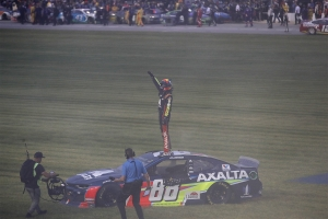 Alex Bowman, driver of the #88 Axalta Chevrolet, waves to the crowd after winning after winning the Monster Energy NASCAR Cup Series Camping World 400 at Chicagoland Speedway on June 30, 2019 in Joliet, Illinois.