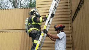 Corey McLaughlin holds the ladder for Assistant Chief Vernon McKinnon as he climbs the ladder for the final task in the physical ability test for the Rockingham Fire Department on Monday. See the RO's Facebook page for the video.