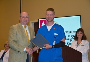 Richmond Community College nursing assistant student Nicholas Davis shakes hands with Dr. Dale McInnis, president of the College, during the pinning ceremony held for students completing the program. Pictured also is Ann Hudson, an instructor for the Nursing Assistant program.