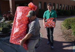 Cascades employees Brian King and David Sheppard carry presents out to a utility trailer. The gifts are for 50 Richmond County foster children. See a video at the bottom of this story.