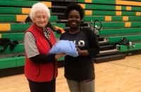 Norma Gwen Garris (left), the mother of Gay Garris Rhyne, awards a winner from last year's tournament with a t-shirt.