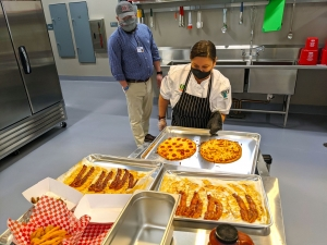 U.S. Foods Division Chef Jennifer Leamons pulls pizza from the oven for Richmond Community College Café Manager Chuck Watson and sets it with other food to be considered for the café's menu.