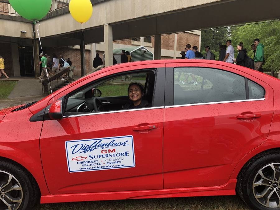 Paulo Zenteno and her newly-won bright red Chevrolet Spark, compliments of Diffenbach Chevrolet/GM