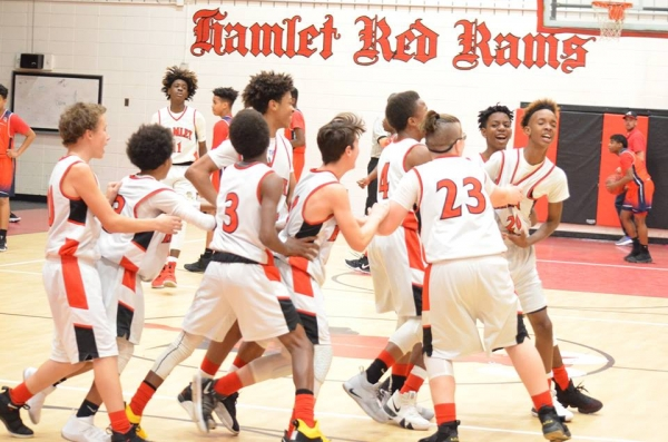 The Red Rams celebrate Paul McNeil's (20) 40-foot buzzer beater at the end of the first quarter Thursday.