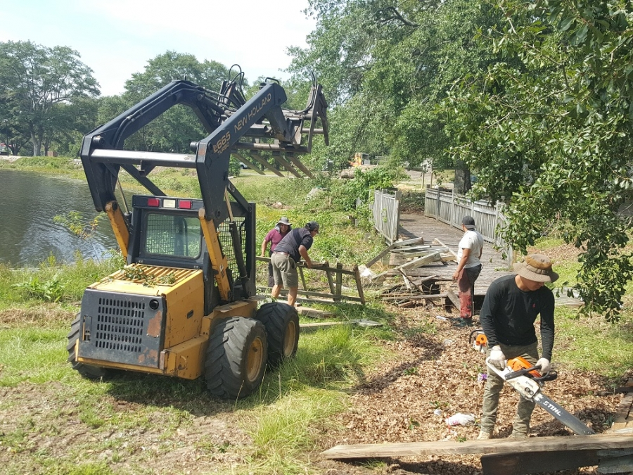 A contracted crew cleans up around Hamlet City Lake on the first day of the first phase of a major renovation project.