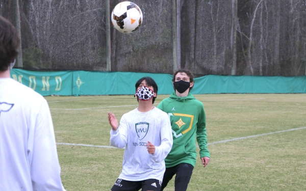 Junior Alex Medina uses his chest to control the ball while fellow junior Cody Eason works defense during Monday's tryout.