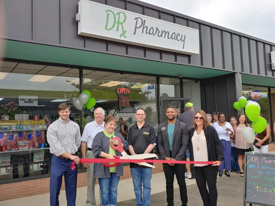 Cristi Tillis snips the ceremonial ribbon in front of her new business, Dr. Pharmacy in downtown Rockingham. Pictured, from left: Neil Robinette, chairman of the Richmond County Chamber of Commerce; Rockingham Mayor Steve Morris; Tillis; Todd Tillis, husband and owner of Todd's Computers; Richmond County Commissioner Tavares Bostic; Chamber President Emily Tucker.