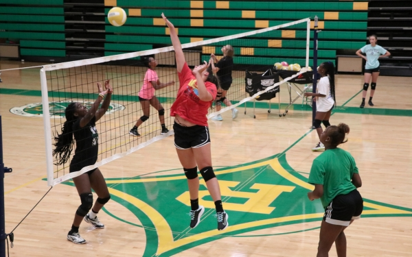 Rising sophomore Catherine Dennis (red) delivers a kill during a small-sided game Tuesday, while teammates Allyiah Swiney (left) and Jakerra Covington (right) watch.