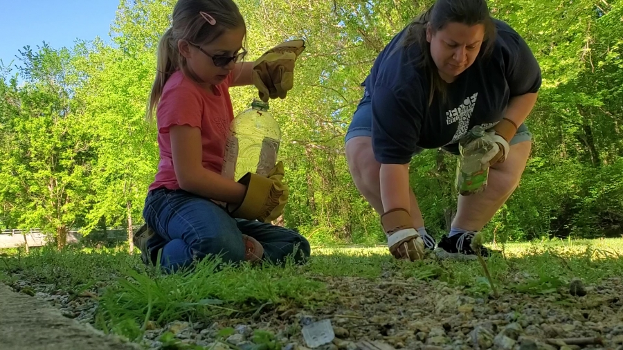 Kelly Chandler, right, and her daughter, Kaylynne, pick up trash around the picnic area of the Hitchcock Creek Greenway for Earth Day.