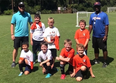 Coach Kyle Baker (left) and members of the new ACS U10 soccer team in Richmond County.