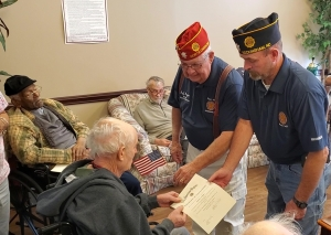 Jeff Joyner and Wayne Johnson present Sammy Lampley with with a flag and certificate of appreciation on behalf of the American Legion for his service in the military during a ceremony at Hamlet House on Monday. The American Legion made a Veterans Day presentation at Richmond Pines Health Care and Rehabilitation.