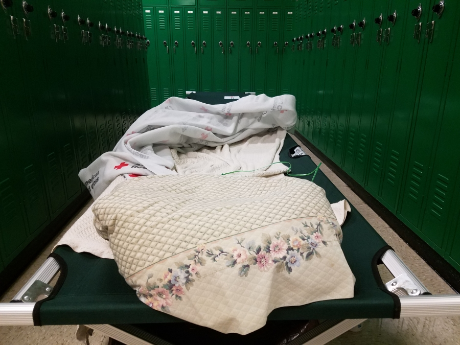 Two green cots sit between locker rows the shelter set up at Richmond Senior High School late Thursday. As of 9 p.m., the shelter was nearly at half-capacity.