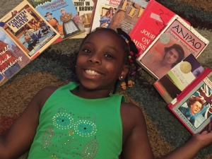 Gabrielle McDonald, a rising third grader at Monroe Avenue Elementary, lies surrounded by books in the media center during Thursday's open house.