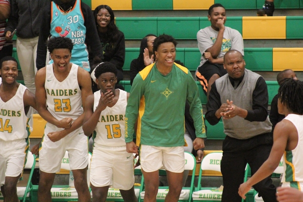 Members of the Raider bench celebrate during the first quarter following Rod Newton's (far right) 11-point outburst.