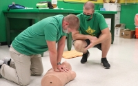 Athletic trainer Mitch Hadinger (right) teaches a CPR certification course to soccer coach Chris Larsen on Tuesday.