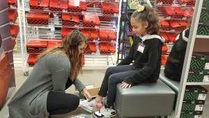 J.C. Penney Associate Brooke Coble helps Fairview Heights Elementary student Destiny Benel try on a pair of sparkly Converse sneakers Thursday morning. Destiny is one of more than 700 students who received a new pair of shoes courtesy of First Presbyterian Church.