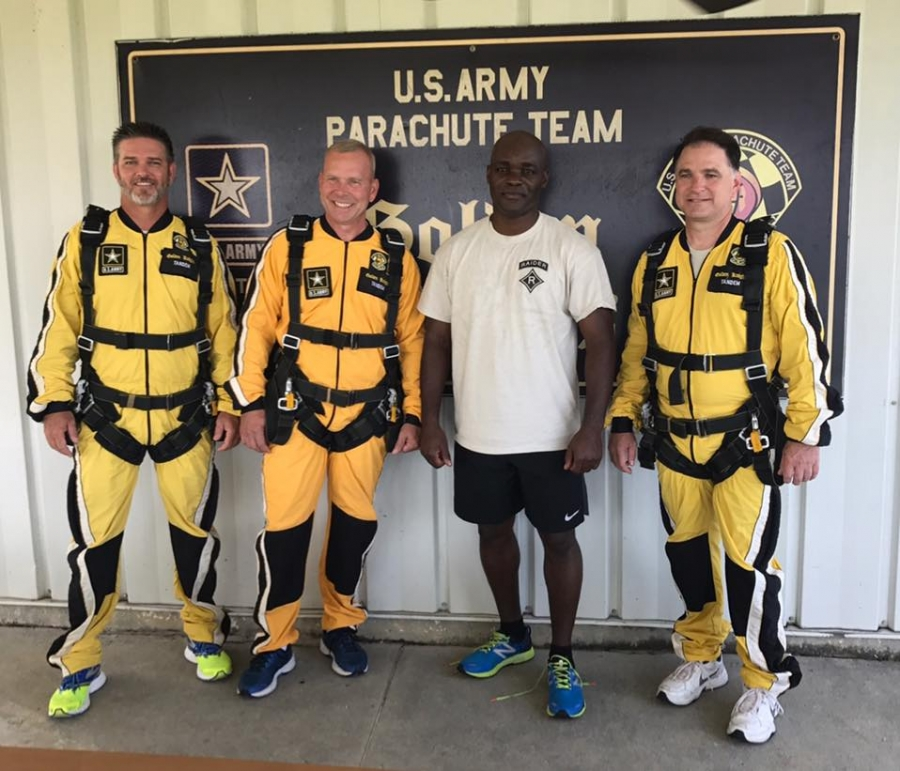 RSHS' athletic director Ricky Young, JROTC directors LTC. Jon Ring and 1SG Aaron Light, and principal Jim Butler pose in front of the U.S. Army's Golden Knights Parachute Facility.