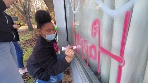 "Tenth-grade Beta Club member Honesty Horne writes ""Happy Holidays"" backwards so it can be read from the inside of a window at PruittHealth Rockingham."