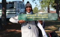 Eleven-year head coach Reggie Miller holds a sign made by this year's team as he coached his final XC race last Saturday.
