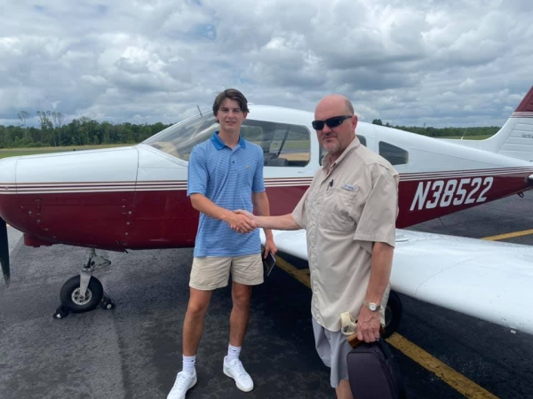 Cole Deane shakes hands with examiner Greg Hudson after earning his private pilot license on Thursday.
