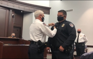 Rockingham Police Chief Billy Kelly pins the Medal of Valor on Officer James Hooks during Tuesday's City Council meeting. Hooks was awarded the medal for taking down a man who allegedly pointed a gun at officers on July 2 near the police station.