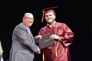 James Moree accepts his high school diploma from Dr. Dale McInnis, president of Richmond Community College. Moree also received the Joseph R. Kester Excellence in Education Scholarship, which is given to the student who has the highest overall grade average among High School Equivalency and Adult High School diploma students.