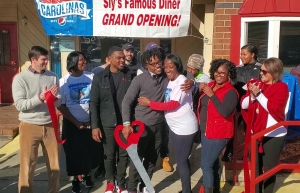 DeMarcus Hough embraces his mother, Linda, after cutting the ribbon in front of Sly's Famous Diner on Friday, joined by family, friends and the Richmond County Chamber of Commerce. See a video at the bottom of this post.