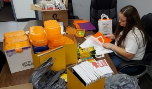 Stephanie Holder, an intern with the Hamlet Police Department, fills bags with school supplies for an event on Saturday.